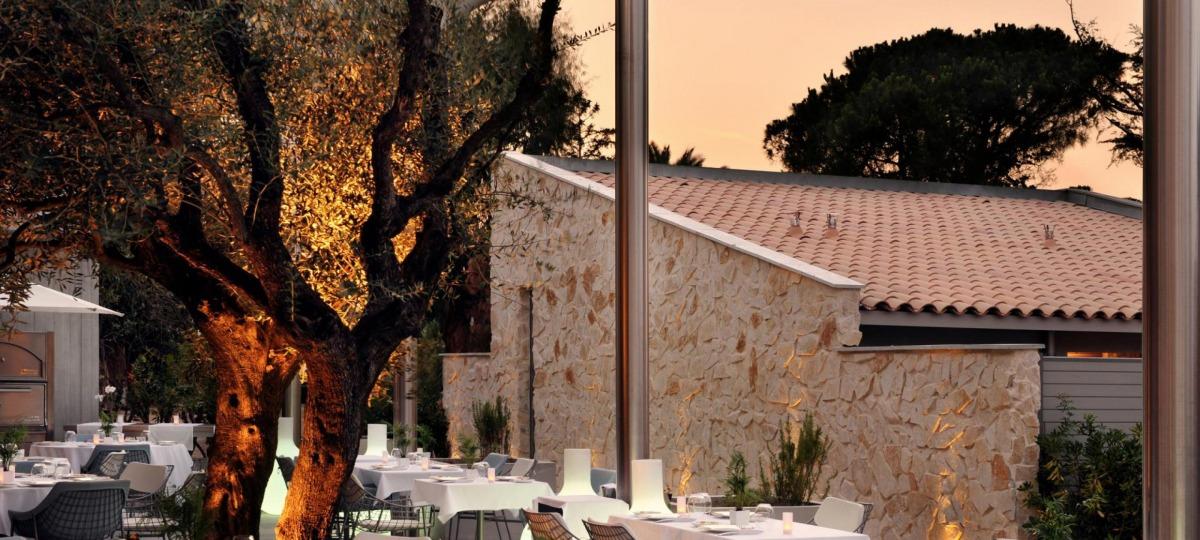 Dinieren Sie in entspannter, festlicher Atmosphäre umgeben von Olivenbäumen und Palmen und mit Blick auf den Pool